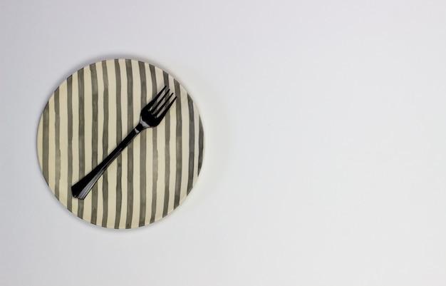 Un piatto e una forchetta su uno sfondo bianco. minimalismo.