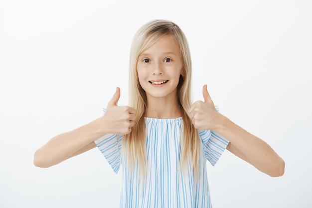 Un piccolo amico solidale vuole rallegrare i compagni. felice ragazza carina positiva con i capelli biondi, alzando i pollici in su e dando approvazione, sorridendo ampiamente mentre mi piace la grande idea, in piedi sopra il muro grigio
