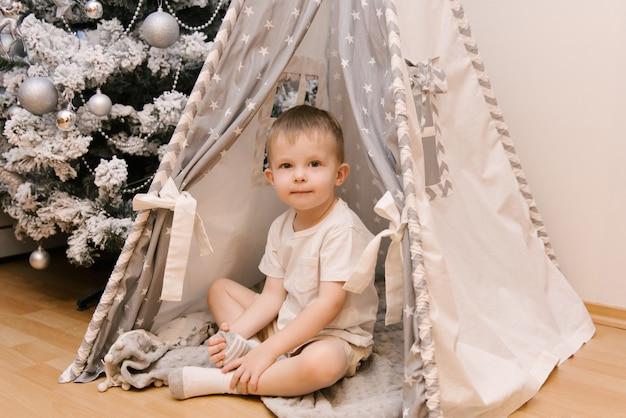 Un piccolo bambino carino è seduto nella stanza dei bambini in una tenda lodge wigwam accanto all'albero di neve di natale