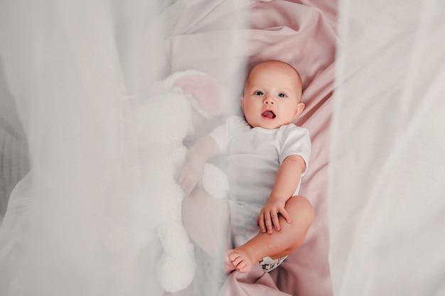 Un piccolo bambino giace su un letto con un coniglio giocattolo e sorride