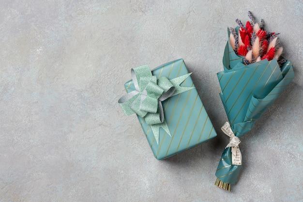 Un piccolo bouquet di lavanda con lagurus e un regalo in confezione turchese con copyspace.