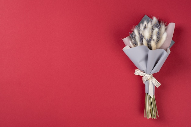 Un piccolo bouquet di lavanda con lagurusn sfondo rosso con spazio di copia.