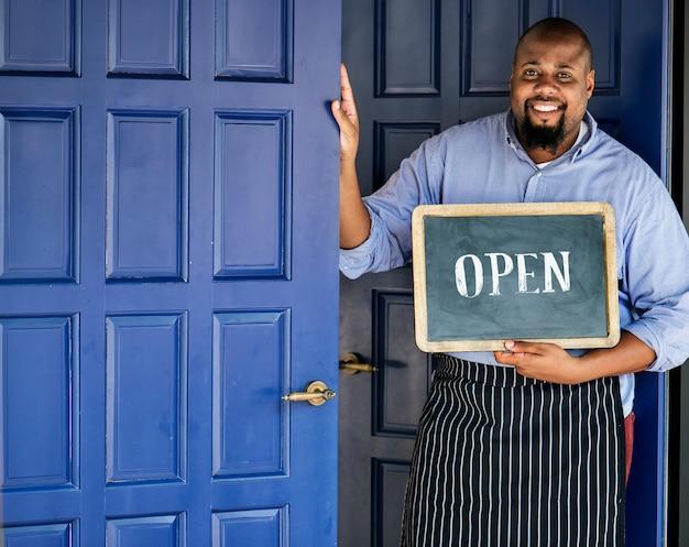 Un piccolo imprenditore allegro con segno aperto