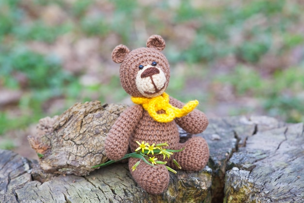 Un piccolo orso bruno con una sciarpa gialla. giocattolo lavorato a maglia, fatto a mano, amigurumi