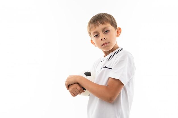 Un piccolo ragazzo biondo tiene il pallone da calcio, immagine isolata