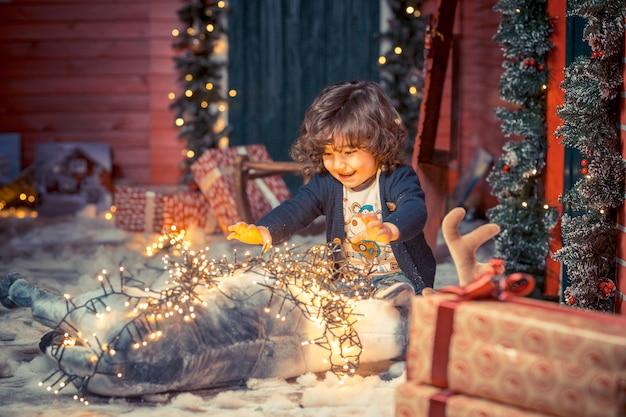 Un piccolo ragazzo dolce bambino riccio in jeans che giocano con il giocattolo dei cervi e le luci di natale nel soggiorno su natale