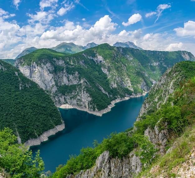 Un pittoresco lago turchese può essere visto dalla cima di un'alta montagna.