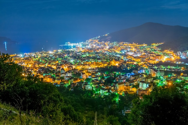 Un pittoresco panorama della città notturna dalla cima della montagna