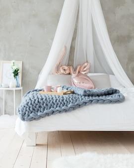 Un plaid grigio di lana merino giace sul letto.
