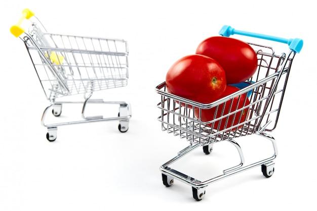 Un pomodoro nel carrello isolato su sfondo bianco. pomodori rossi saporiti maturi in carrello. concetto commerciale di pomodoro. concetto di shopping online. carrello e pomodoro su uno sfondo bianco.