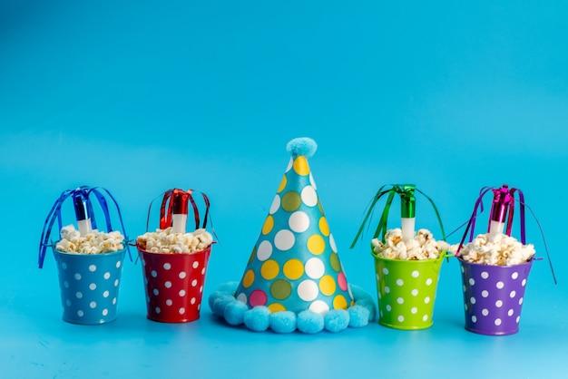 Un popcorn fresco con vista frontale all'interno di cestini colorati insieme al berretto di compleanno su chicchi di snack di film cinematografici blu