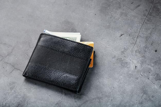Un portafoglio nero con banconote e una carta elettronica dorata su pietra grigio scuro.