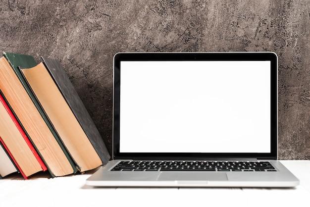 Un portatile aperto con vecchi libri antichi hardcover sulla scrivania contro il muro di cemento