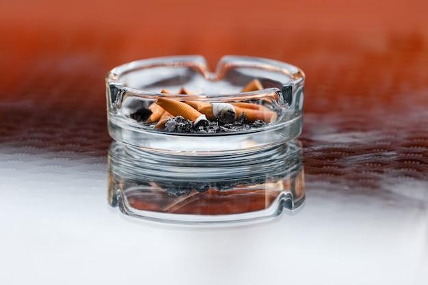 Un posacenere sporco con cenere di sigaretta e mozziconi