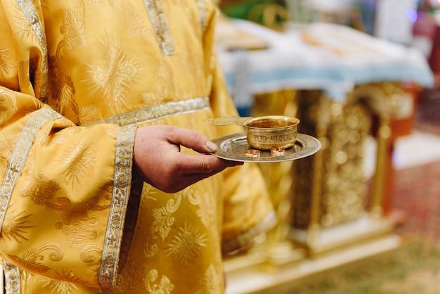 Un prete in chiesa con in mano un vassoio con fedi nuziali