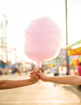Un primo piano della mano di due donne che tiene il filo di caramella rosa