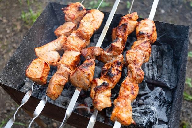 Un primo piano delle torte di maiale in salsa viene fritto in una griglia.