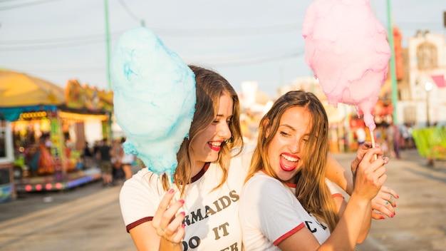 Un primo piano di due amici femminili felici con zucchero filato al parco di divertimenti