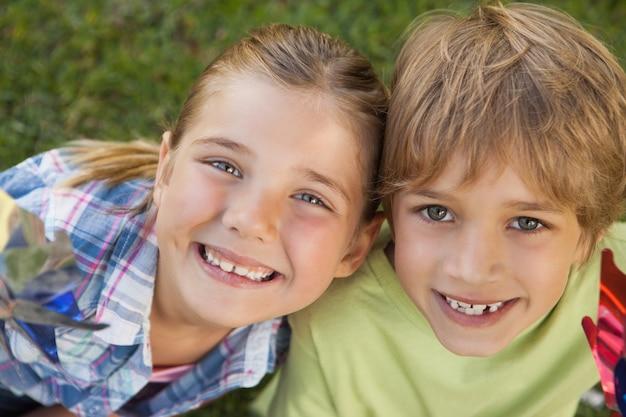 Un primo piano di due bambini che tengono le girandole nel parco