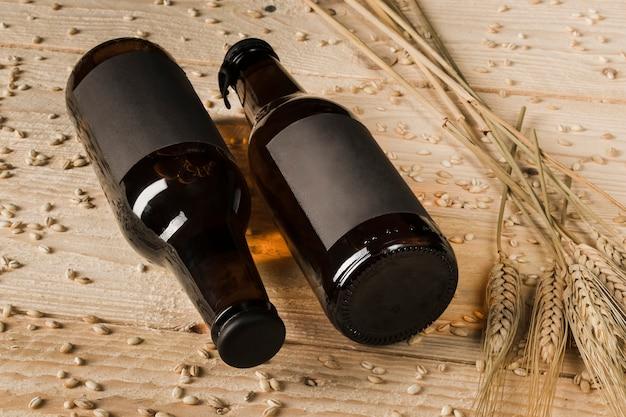 Un primo piano di due bottiglie da birra e spighe di grano su fondo di legno