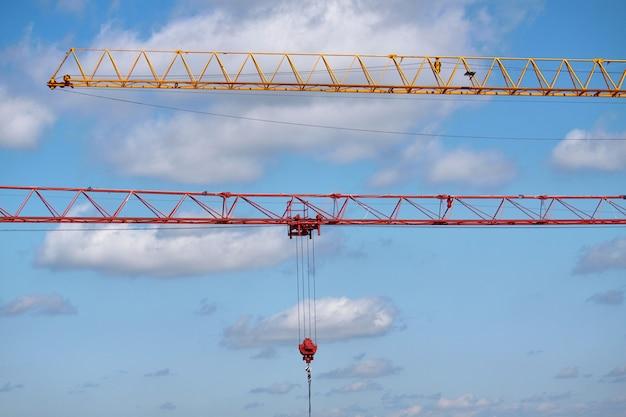 Un primo piano di due frecce delle gru di costruzione ha organizzato parallelamente contro un cielo blu, fuoco selettivo
