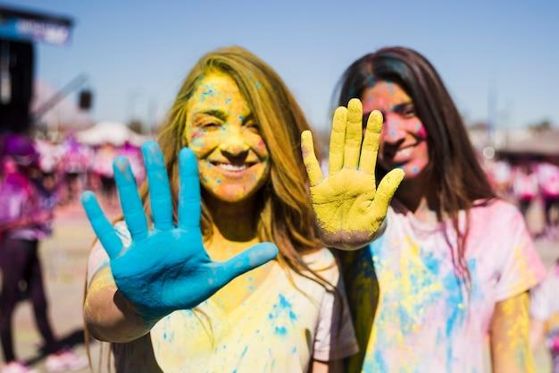 Un primo piano di due giovani donne che mostrano le loro mani dipinte con il colore di holi