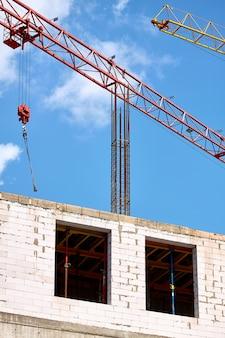 Un primo piano di due gru a torre che lavorano sullo sfondo di una nuova costruzione e di un cielo blu, fuoco selettivo