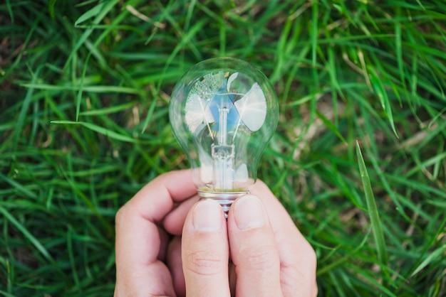 Un primo piano di due mani che tengono lampadina contro l'erba verde