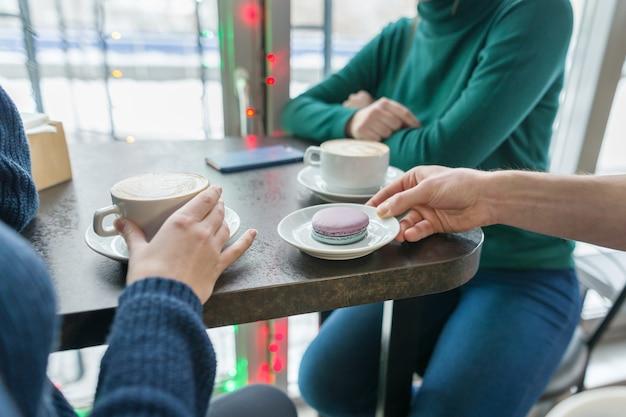 Un primo piano di due mani delle donne con le tazze di caffè