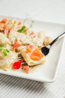 Un primo piano di paccheri con salsa di panna e salmone su una forchetta, su un piatto bianco