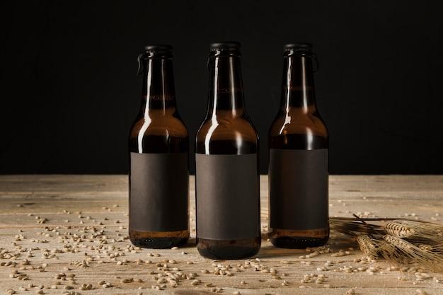 Un primo piano di tre bottiglie da birra e spighe di grano sul contesto di legno