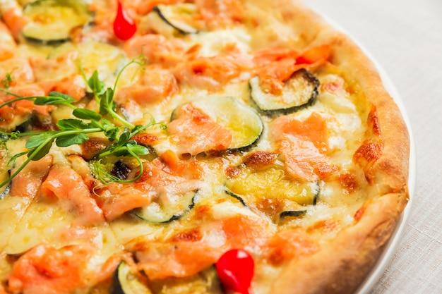 Un primo piano di una pizza con zucchine, pesce rosso e formaggio, su un piatto bianco