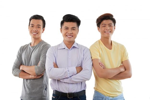 Un primo piano medio di tre amici asiatici in piedi braccia conserte