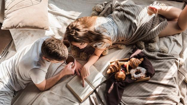 Un punto di vista elevato delle coppie che si trovano sul libro di lettura del letto