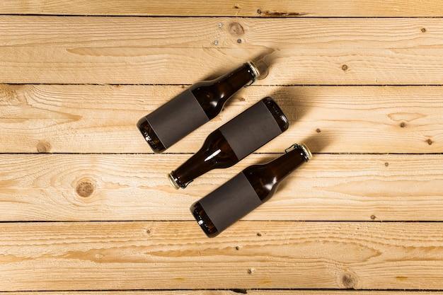 Un punto di vista elevato di tre bottiglie di birra su fondo di legno