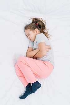 Un punto di vista elevato di una ragazza malata che indossa calzino con dolore allo stomaco