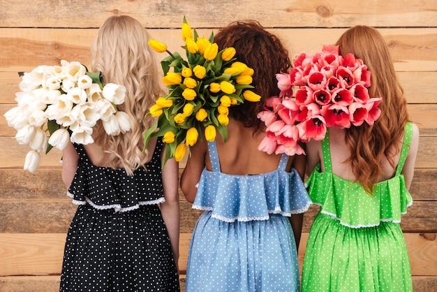 Un punto di vista posteriore di tre donne che tengono i fiori dei mazzi