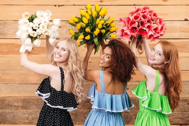 Un punto di vista posteriore di tre giovani donne che tengono i fiori dei mazzi