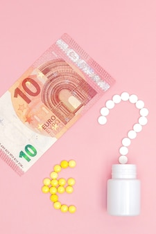 Un punto interrogativo e un segno di euro disposti di pillole e 10 euro su una parete rosa. concetto di medicina, denaro e salute