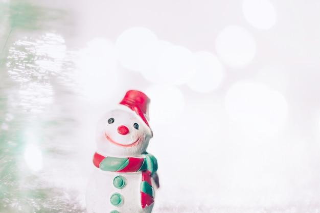 Un pupazzo di neve in miniatura su priorità bassa di natale. cartolina d'auguri di natale con lo spazio della copia.