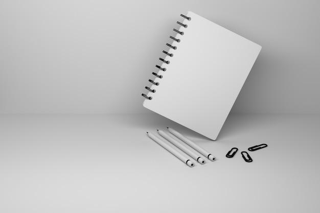 Un quaderno a spirale con copertina vuota e tre matite