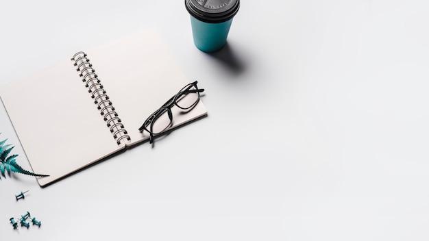 Un quaderno a spirale vuoto aperto con gli occhiali; tazza di caffè usa e getta e puntine su sfondo bianco