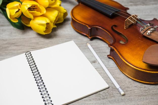 Un quaderno bianco aperto; matita; tulipano e violino classico sullo sfondo della plancia