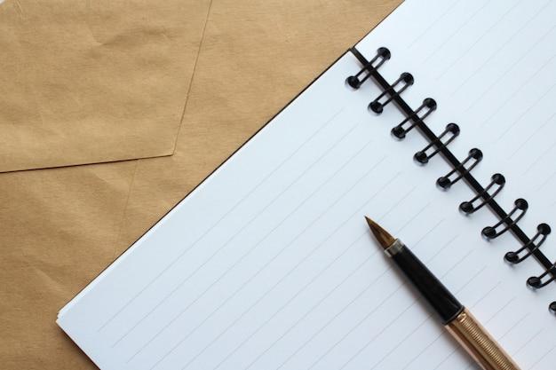 Un quaderno con fogli puliti, una busta e una penna d'oro sul tavolo