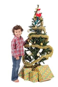 Un ragazzino ad adornare il suo arbol di natale così che babbo natale arriva con i regali