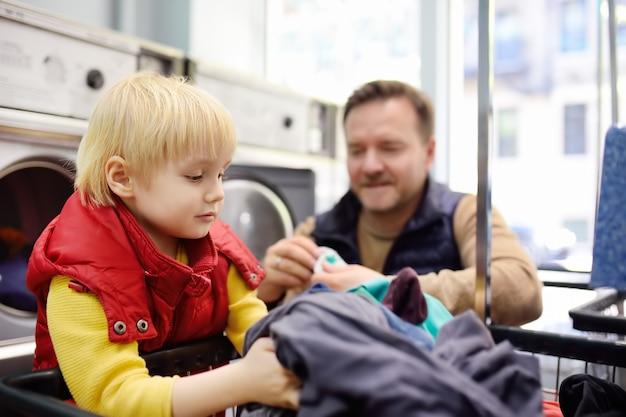 Un ragazzino carica i vestiti nella lavatrice nella lavanderia pubblica