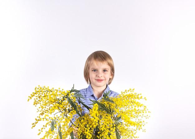 Un ragazzino carino è in possesso di un mazzo di mimosa gialla. un regalo per la mamma. congratulazioni per l'8 marzo, festa della mamma.
