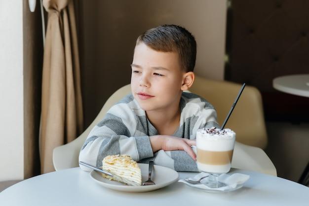 Un ragazzino carino è seduto in un bar e guardando una torta e il primo piano di cacao. dieta e corretta alimentazione.