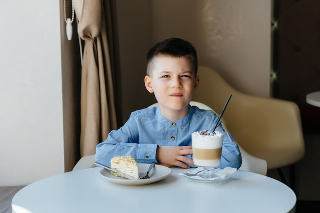 Un ragazzino carino è seduto in un bar e guardando una torta e il primo piano di cacao.