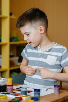 Un ragazzino carino sta giocando e dipingendo nella sua stanza. divertimento e intrattenimento. resta a casa.